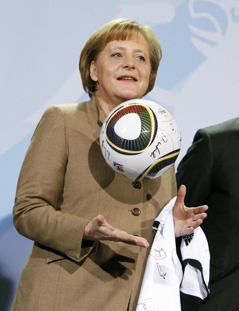 File photo German Chancellor Merkel holding soccer ball and jersey of national squad with signatures of players at Chancellery in Berlin